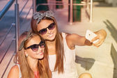 Two girls  taking photos with a smartphone — Stockfoto