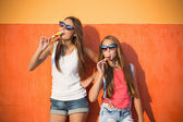 Two girls with ice-cream on background wall — Stock Photo