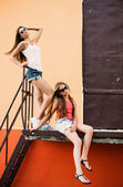 Two teenager girls on background wall — Stock Photo
