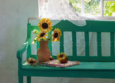 Sunflowers on wooden bench — Stock Photo