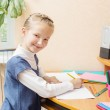 Cute smiling girl sitting at desk — Stock Photo #50408619
