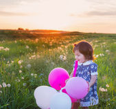 Little girl with balloons outdoor — Stock Photo