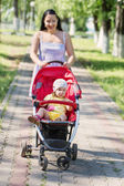 Happy young mother with baby in buggy walking in park — Stock Photo