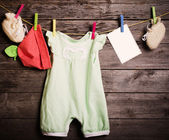 Children's clothing and paper on a wooden background — Stock Photo