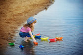Child playing with paper boats in the water — Stock Photo