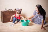 Little girl and mother with old suitcase indoor — Stock Photo