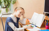 tired schoolgirl studying with book on her desk — Stock Photo