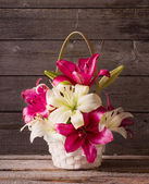 lily in basket on wooden background — Stock Photo