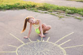 The child drawing a chalk on asphalt — Stock Photo