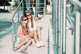 Two girls  taking photos with a teletphone — Stok fotoğraf