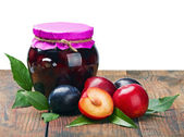 Canned fruit compote and fresh plums — Stock Photo