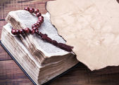 Bible with rosary and old burnt piece of paper — Stock Photo