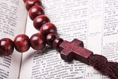 Rosary with a wooden cross lying on open Bible — Стоковое фото