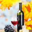 Bottle, glass of red wine and assorted cheeses — Stock Photo