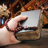 Hands holding the Bible and praying with a rosary — Stock Photo
