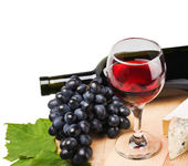 Glass of red wine with grapes — Stock Photo