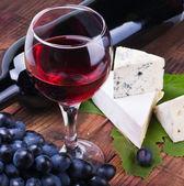 Verre de vin rouge avec bouteille et raisins — Photo