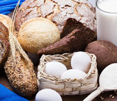 Fresh eggs and a lot of different breads — Stock Photo