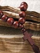 Rosario de madera están en una vieja biblia — Foto de Stock