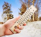 Ręka trzyma termometr z nisko przed zimnem wint — Zdjęcie stockowe