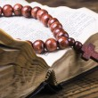Wooden rosary and the Bible - Stock Photo
