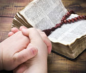 Human hands holding the Bible and praying with a rosary — Stock Photo