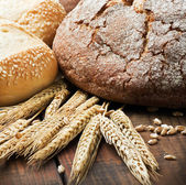 Fresh bread and rolls with ears of wheat on the table — Stock Photo