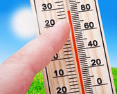 Thermometer in hand, shows a strong heat — Stock Photo