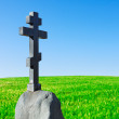 Stone cross on a pedestal stands in a field — Stock Photo