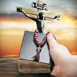 Hand holds the bible on the background of the Crucifixion of Jes - Stock Photo