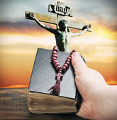 Hand holds the bible on the background of the Crucifixion of Jes — Stock Photo