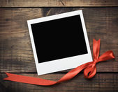 Photo frame with a red bow — Stock Photo