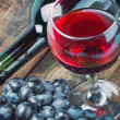 Stock Photo: Glass of red wine with bottle and grape