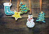 Christmas gingerbread cookies hanging over wooden background — Stock Photo