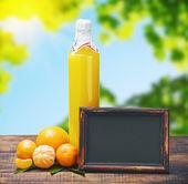 黒板と柑橘系の果物からジュースの瓶 — ストック写真