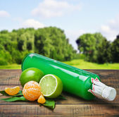 Bottle with the juice of citrus and lime — Stock Photo