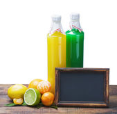 Bottles of juice from citrus fruits and blackboard — Foto de Stock