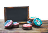 Blackboard and chocolate cakes with icing for text — Stock Photo