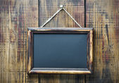 Blackboard on wooden background with space for text — Stock Photo