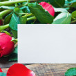 Red roses and white card with a place for a congratulatory text — 图库照片