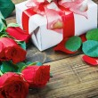 Red roses and gift for Valentine — Stockfoto #17187393