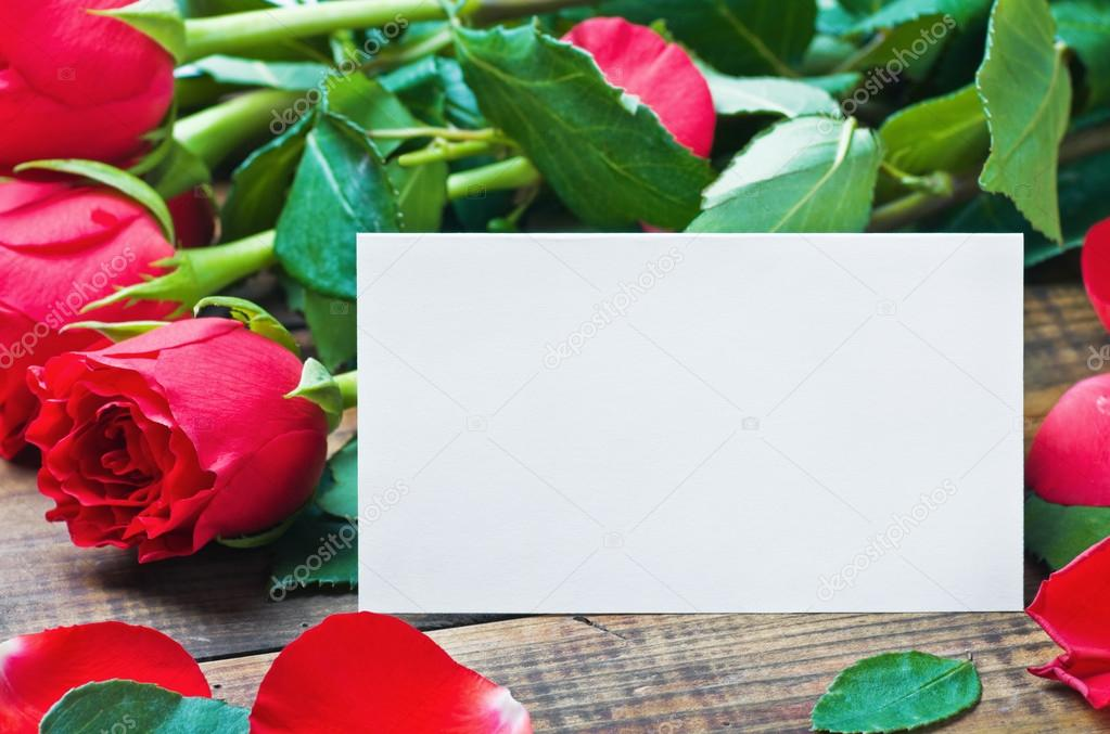 Red roses and white card with a place for a congratulatory text on a wooden table — Foto Stock #17187203