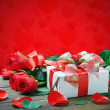 Fresh red roses and a gift isolated on a red background — Foto Stock