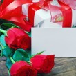 Red roses and white card with a place for a congratulatory text - Stock Photo