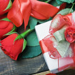 Red roses and holiday gift — Stock Photo