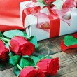 Roses and holiday gift on a wooden table — Stock Photo
