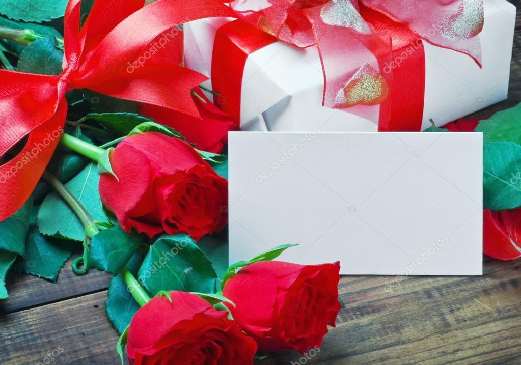 Red roses and white card with a place for a congratulatory text on a wooden table  — Stock Photo #17686173