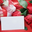 Foto Stock: Roses and white card with a place for a congratulatory text