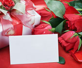 Roses and white card with a place for a congratulatory text — Stock Photo