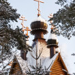 Wooden church and the golden domes of the winter pine forest — Foto Stock